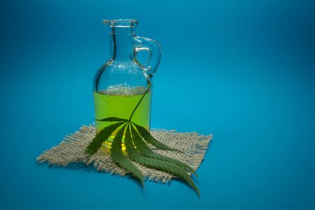 Cannabis leaf and glass decanter on a square of hessian. Cannabis Oil - medical marijuana concept 스톡 콘텐츠