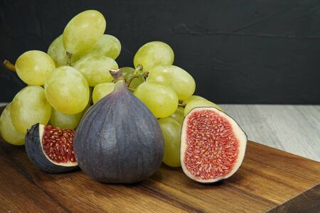 Fresh tropical fruit still life with juicy ripe purple figs and bunches of red and green grapes on a wooden table