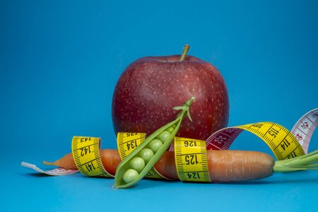 Weight loss and healthy diet concept with measuring tape, carrot, pea pod and red apple on blue background Stock Photo