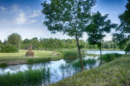 Tranquil lake with large ready built bonfire on the further shore waiting to be lit in the evening for a celebration or party Stockfoto