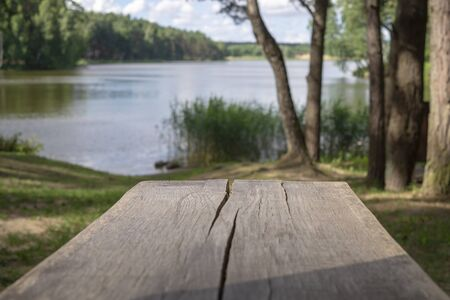 Old cracked weathered wooden picnic table outdoors overlooking a tranquil like or river with shady trees