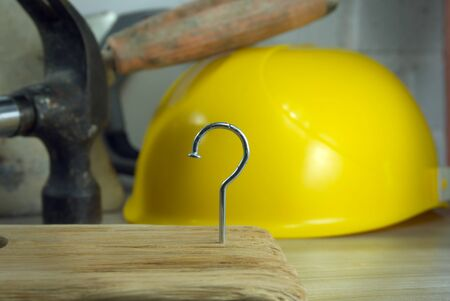 Construction nail shaped as question mark with blurred background of various tools and helmet, construction questions and confusion concept