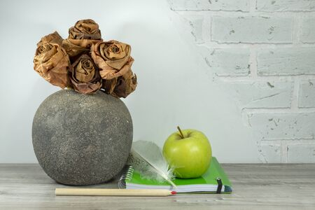 Back to school concept with green spiral ring bound notebook, apple, pencil and quill pen on the table against a white brick wall with free copy space