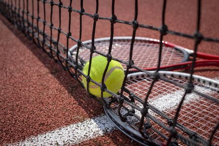 Tennis scene with black net, ball and racquets on red hard court surface