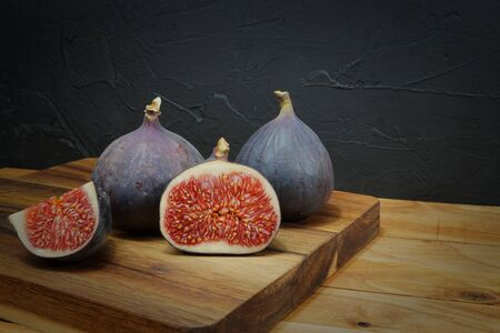 Ripe, purple figs on wooden table with sliced one fig 写真素材