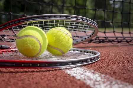 Two tennis balls resting on top of a tennis racquet on a red hard court, low angle view and selective focus Фото со стока