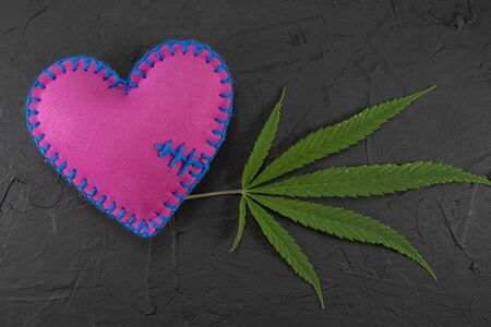 Handmade colorful felt bright pink textile heart with a fresh green marijuana leaf over a black background with copy space in a conceptual image