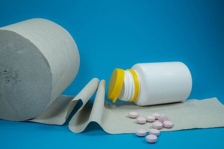 Healthcare, drugs and medication concept with scattered pink pills beside an overturned plastic pharmacy bottle on a large roll of paper towel over a blue background with copy space Stok Fotoğraf