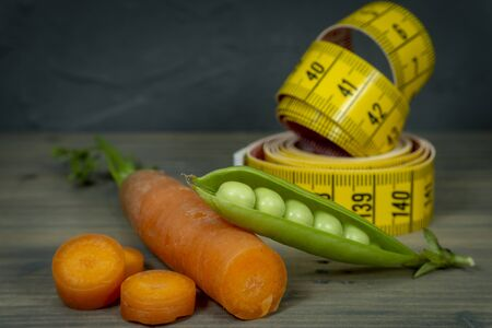 Weight loss and healthy diet concept with carrot, pea pot and measuring tape on wooden background Stock Photo
