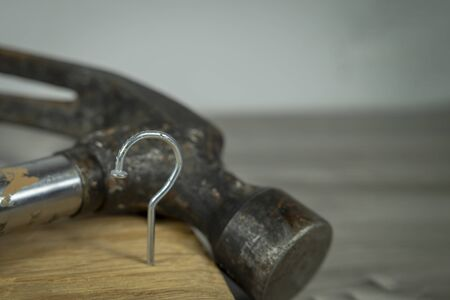 Construction nail shaped as question mark with blurred background of hammer, construction questions and confusion concept