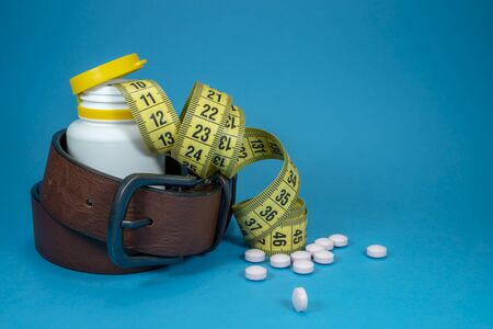 Conceptual weight loss image with a tape measure, scattered pills and genuine leather belt wound around a pharmacy bottle over blue