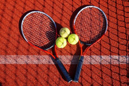 Top view tennis scene with balls, racquets, net shadow and hard court surface line