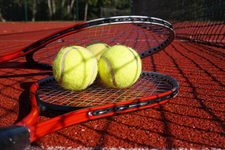Tennis scene with black net shadow, tennis balls resting on top of a tennis racquet on red hard court surface, low angle view and selective focus
