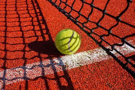 Detail of a tennis ball and black net at the hard court surface corner line Фото со стока
