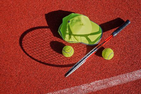 Tennis racket standing on end casting a shadow over an all weather outdoor court, peaked cap and balls in a sports and healthy lifestyle concept