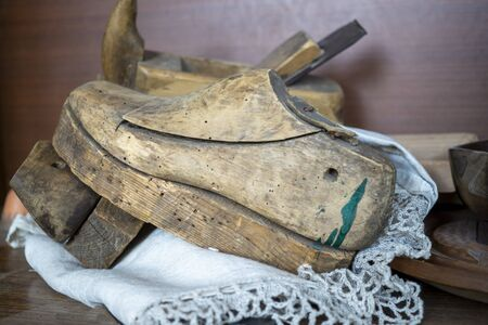 Old vintage wooden shoe mold or last on a lacy mat on a workbench with assorted tools behind in a close up side view
