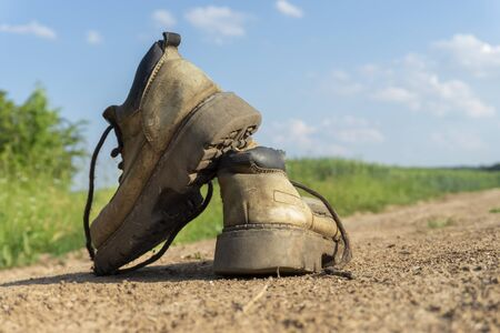 Pair of old worn leather hiking boots an a gravel path or road balanced on top of one another in a close up view Foto de archivo