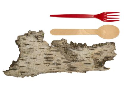 Isolated piece of wood and tree bark with wooden eating utensils, a natural spoon and red fork, above with copy space in a protect nature conceptual image