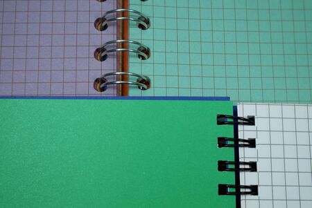 Wire bound open notebook ruled with squares lying on a second open notebook with green and purple pages in a conceptual image for business or education