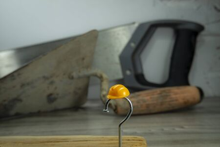 Construction nail shaped as question mark with yellow plastic workplace helmet and blurred background of various construction tools, construction questions, confusion and work safety concept