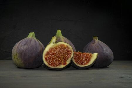 Ripe, purple figs on wooden table with sliced one fig Stock Photo