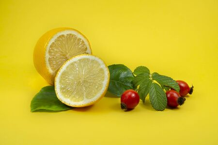 Cut in half lemon with green leaves and rose hips berries on yellow background, natural remedies for cold and flu season Stock Photo