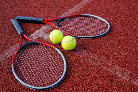 Tennis scene with balls, racquets and hard court surface corner lines
