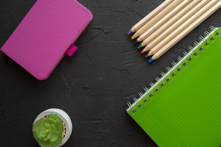 Back to school background with green spiral ring bound notebook, pink notebook and pencils on black background. Flat lay, view from above