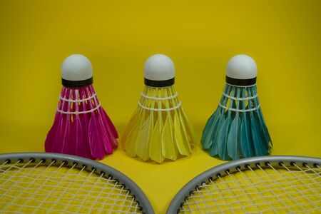 Badminton rackets and colorful feathered shuttlecocks in blue, yellow and pink