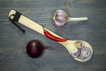 Raw onion, garlic and chili pepper recipe concept with wooden spoon for decoration, viewed from above on dark wooden table background Stock fotó