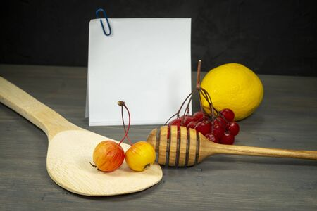 Autumn still life with apples, redcurrant berries, lemon and honey wand in front of a blank upright card with copy space, recipes concept