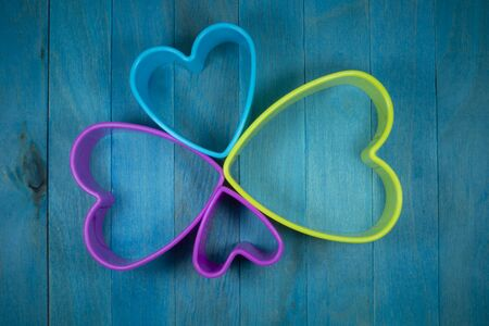 Colored heart-shaped cookie cutter figures forming a decorative flower, sitting on blue wooden background and viewed from above Imagens