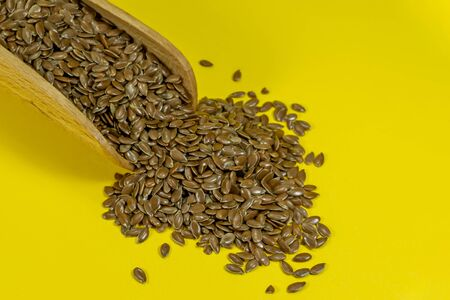 Flax seeds spilling from a wooden scoop, copy space on yellow background Imagens