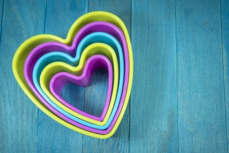 Colored heart-shaped cookie cutter figures sitting on blue wooden background and and viewed from above