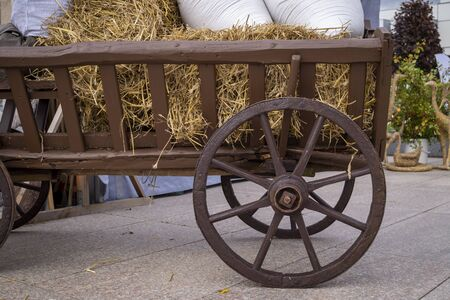 Autumn display with an old rustic wooden wagon with spokes on the wheels and bales of fresh hay loaded with white sacks in a courtyard or sidewalk