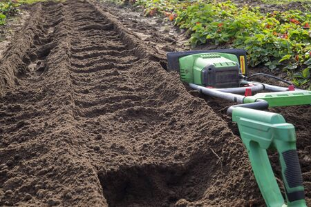 Power cultivator or tiller machine handle in close-up with a just ploughed furrow in background Stockfoto