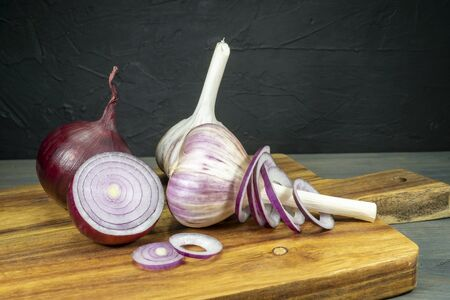 Red onion, whole and sliced in rings and garlic sitting on wooden cutting board and viewed in closeup, from low angle Stockfoto