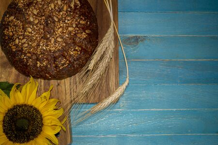 Bread with various seeds, ear of ripe wheat and sunflower blossom on wooden cutting board