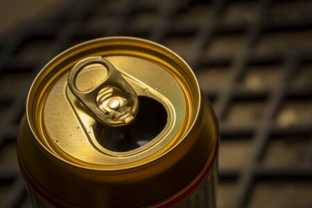 Opened can of beer or soda water with golden coloured aluminium top. Close-up view from high angle with copy space Imagens