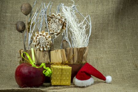 Christmas still life with colorful red Santa Hat, decorations, gold wrapped gift and apple over a hessian or burlap background with copy space for a seasonal greeting Stockfoto