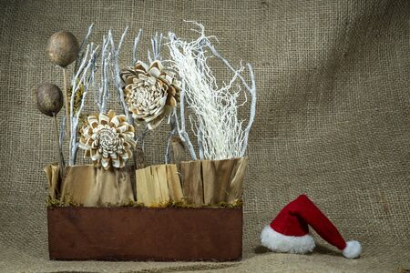 Christmas still life with colorful red Santa Hat, decorations over a hessian or burlap background with copy space for a seasonal greeting Stockfoto