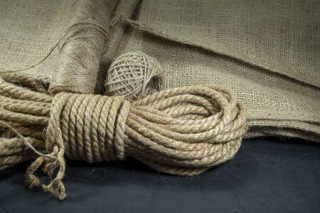 Spools of burlap threads or jute twine, sackcloth fabric in close-up on rustic grey background Stockfoto