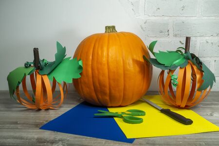 Halloween handicraft concept making homemade decorations from colorful paper and a large fresh pumpkin on a wooden table over a white brick wall Imagens