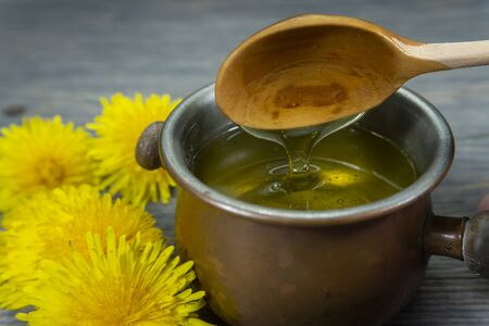 Pot of honey dripping off a spoon with colorful yellow spring dandelions alongside in a healthy diet concept Stockfoto