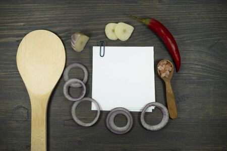 Recipe concept with blank white square of paper note, wooden spoon, raw onion, garlic and chili pepper viewed from above on dark wooden table background