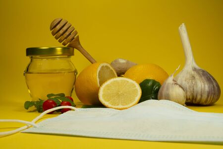 Ingredients for a healthy infusion with disposable face mask, lemon, fresh root ginger, garlic, honey and rose hips over a yellow background, natural remedies for cold and flu season Stockfoto
