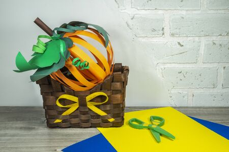Halloween handicraft concept making homemade decorations from colorful paper and a large fresh pumpkin on a wooden table over a white brick wall Stockfoto