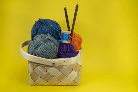 Handicraft and needlework concept - close up of wicker basket with colorful balls of yarn and knitting needles on yellow background with free copy space
