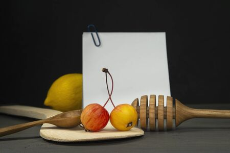 Recipe concept with wild apples, wooden spoon, lemon and honey wand with sticky notes on a gray old wood surface against a dark wall in grunge style