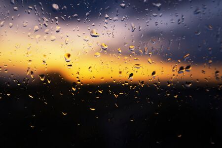 Colorful sunset through wet window glass with beaded raindrops and rivulets of water on a stormy day in a full frame conceptual background
